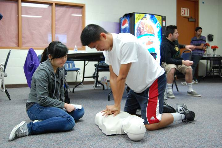 SAVING LIVES  - Juniors Minsong Hsu and Jessica Chang, both participants of the class, practice proper CPR chest compressions and rescue breaths on a dummy.